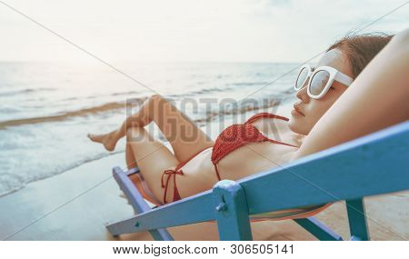 Summer Beach Vacation Concept, Asia Woman With Hat Relaxing And Arm Up On Chair Beach. Young Fashion