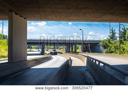 Under The Bridge On The Motorway. Concrete Construction Of Road Junction. Highway In Europe. Between