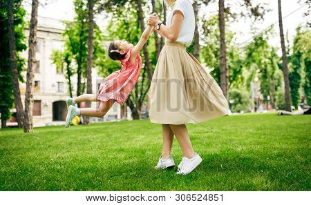 Outdoors Image Of Happy Daughter Playing With Her Mother In The Park. Loving Mother And Her Chid Spi