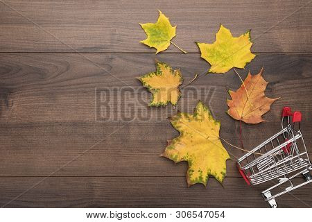 Shopping Trolley Over Wooden Background. Overturned Pushcart And Yellow Autumn Leaves With Some Copy
