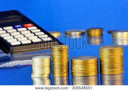 A Stack Of Metal Coins Accountant And A Calculator On A Blue Background. A Coin Is A Monetary Sign M