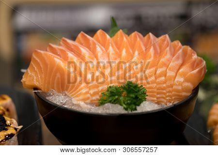 Japanese Food Sashimi Salmon In Black Bowl Decoration With Vegetable On Iced. Sashimi Is Something R