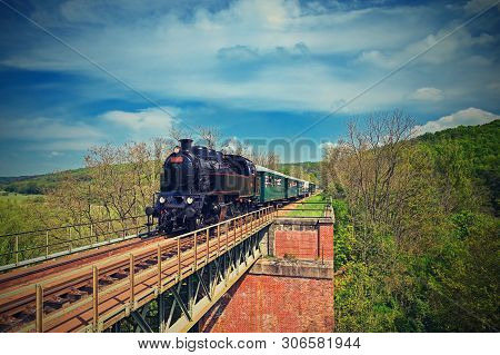 Beautiful Old Steam Train Driving Along A Bridge In The Countryside. Concept For Travel, Transportat