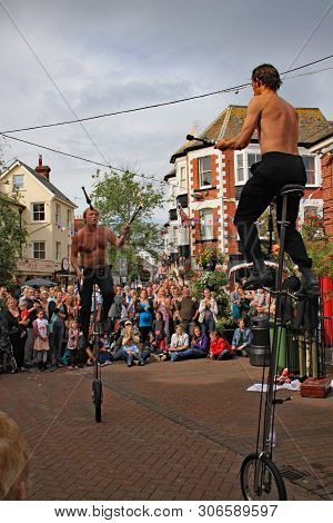 Sidmouth, Devon, England - August 5th 2012: Two Street Jugglers And Entertainers Perform With Unicyc