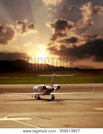 Close up private jet airplane parked at airport over cloudy sunset sky