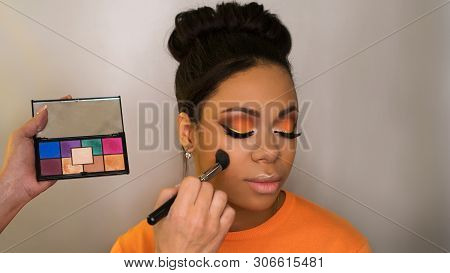 Makeup Artist Working With African American Model In Beauty Salon Face Sculpt. Contouring. Contour A