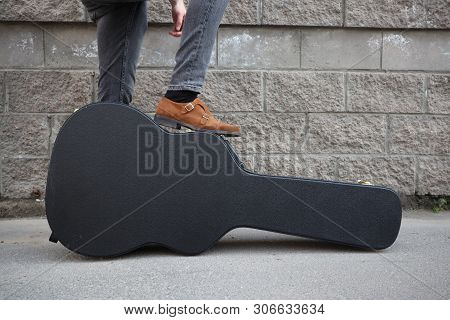 Man Put His Foot On A Hard Guitar Case. Hard Case For Electric Guitar. Man Dressed In Jeans Holding