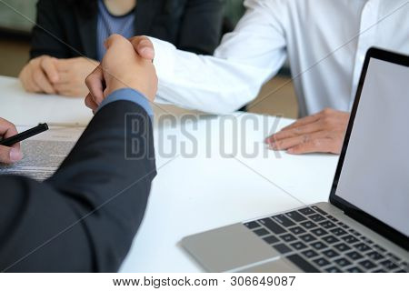 Couple Shaking Hands To Realtor Mortgage Insurance Broker Lawyer. Customer Handshaking With Financia