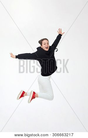 Young Pretty Brunette Girl In Black Hoodie, White Pants And Red Sneakers Jumping Isolated On White B