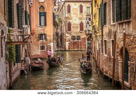 Venice, Italy - May 20, 2017: Gondolas With People Sail On An Old Narrow Canal In Venice. Gondola Is