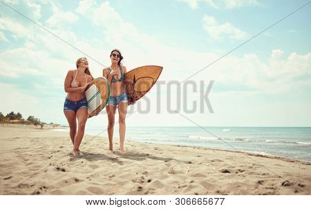 Friends happy surfer girls walking with board on the sandy beach at vacation.