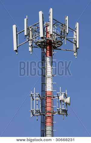Red and white tower of communications with with a lot of different antennas under clear sky.