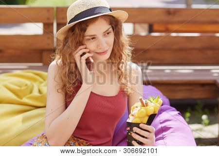 Out Door Shot Of Attactive Young Beautiful Woman With Wavy Hair, Sitting On Frameless Mild Chair In