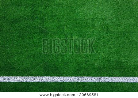 Photo of a green synthetic grass sports field with white line shot from above.