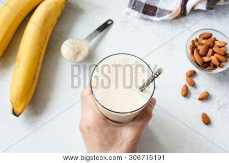 Protein Banana Milkshake Or Smoothie. Mans Hand Holding Glass Of Healthy Vegan Vegetarian Smoothie