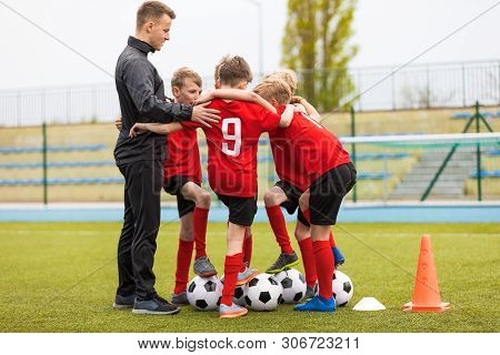 Group Of Happy Boys Making Sports Huddle. Smiling Kids Standing Together With Coach On Grass Sports