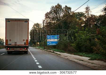 Jucu, Romania - Sep 26, 2013: Romanian Highway With Large Truck Cargo Haulage Near Street Road Sign