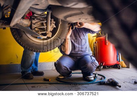 Photo Of  Car Mechanics Fixing The Car. Inside The Car Shop. View From Under The Car