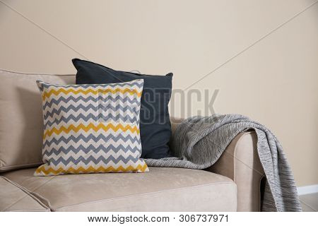 Cozy Sofa With Pillows And Plaid Near Light Wall, Space For Text. Living Room Interior Design