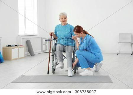 Professional Physiotherapist Working With Elderly Patient In Rehabilitation Center