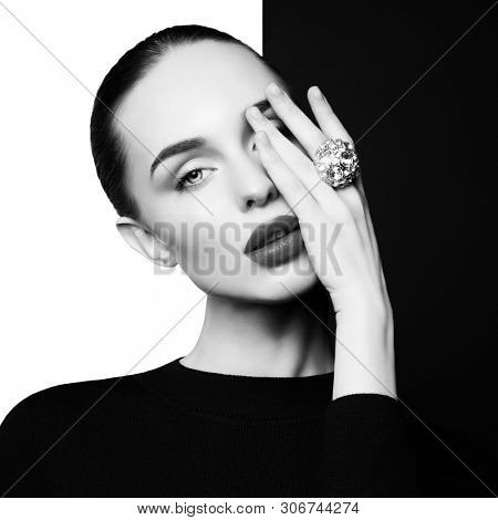 young sexy lady with big ring with diamonds in black-and-white studio. beautiful woman with perfect lips and black lipstick poses in photostudio. Fashion portrait of fashionable model.