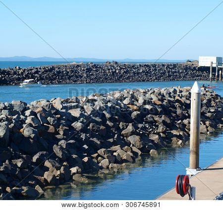 Urungan Marina. Rock Break Or Training Walls At The Marina Entrance. Waterfront Walkway In Tropical
