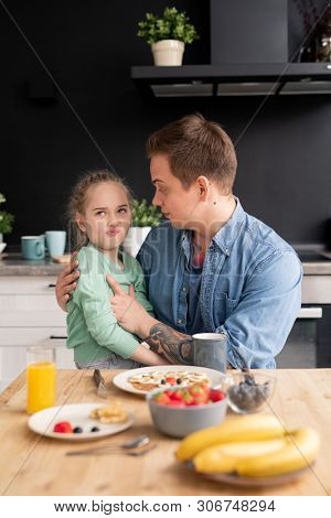 Picky daughter sitting on fathers knees and grimacing while refusing to eat breakfast made by father