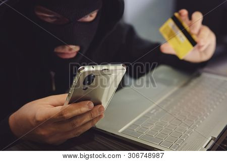 Male Hacker In A Robber Mask Uses Phone, Credit Card And Laptop In Some Fraudulent Scheme. Cyber Thi