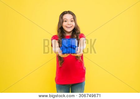 Gift Giving Makes Her Happy. Adorable Little Girl Giving Blue Present Box On Yellow Background. Cute