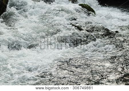 Rapids With Turbulent Water Splashing Over Rocks In A River