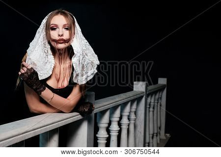 Concept Halloween Makeup. A Sexy Girl Dressed As A Nun Stands On A Balcony Near A White Marble Raili