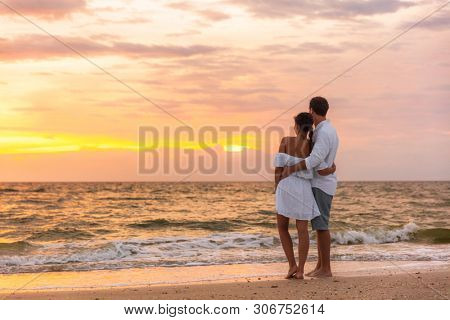 Honeymoon couple walking on sunset romantic stroll on Lover's key beach in Florida enjoying evening light relaxing on tropical summer vacation travel holiday. Two adults silhouettes lifestyle.