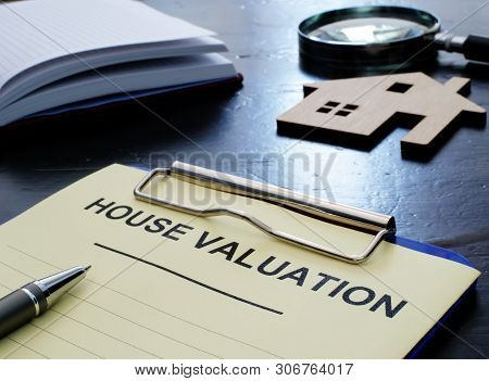 House Valuation Concept. Documents In Clipboard And Small Wooden Home.