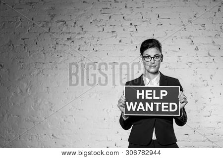 Black and White photo of Portrait of beautiful young businesswoman holding help wanted sign against brick wall