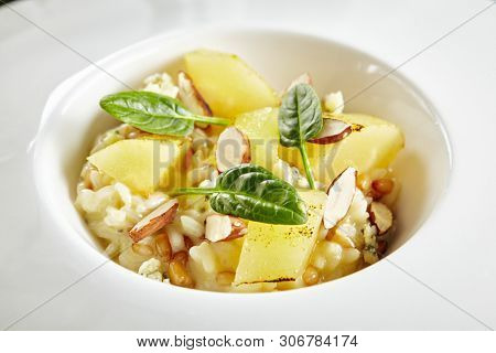 Exquisite Serving White Restaurant Plate of Risotto with Gorgonzola Cheese, Raisins, Almonds and Baked Pear Top View. Beautiful Delicacy Italian Fruit Paella on Dark Stone and Leaves Background