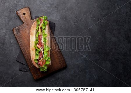 Fresh submarine sandwich with prosciutto ham, cheese and lettuce on dark stone background. Top view with copy space for your text