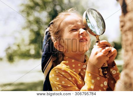 Cute Little Girl Exploring The Nature With Magnifying Glass Outdoor. Child Playing In The Forest Wit