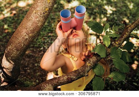 Little Girl Looking Through A Binoculars Searching For An Imagination Or Exploration In Summer Day I