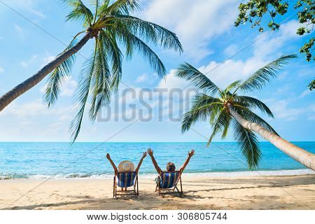 Happy Couple With Arms Up Relax On The Beach Enjoy Beautiful Sea On The Tropical Island. Summer Beac