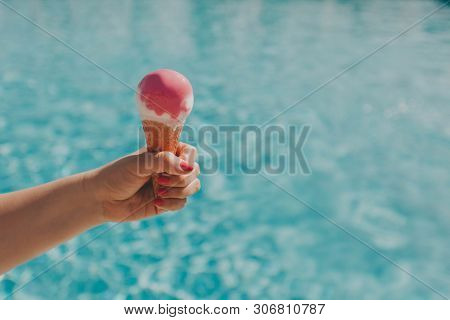 Female Hand With A Beautiful Manicure Holds Pink Ice Cream On A Hot Day On Background Of A Blue Pool