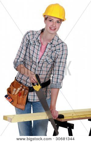 young female carpenter using saw