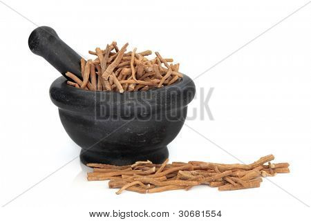 Corydalis tuber used in traditional chinese herbal medicine in a black granite mortar with pestle isolated over white background.