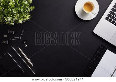 Top View Of Workplace, Coffee Cup With Laptop, Diary And Phone On Black Table