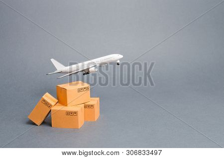Airplane And Stack Of Cardboard Boxes. Concept Of Air Cargo And Parcels, Airmail. Fast Delivery Of G