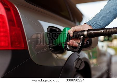 Hand Of Anonymous Man Putting Nozzle Into Tank While Refueling Modern Vehicle With Premium Quality G
