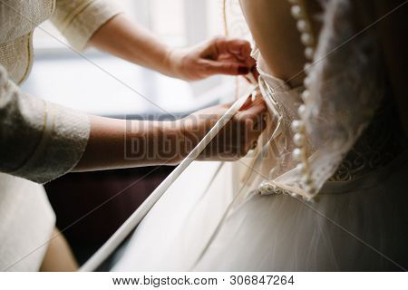 A White Wedding Dress Is Knitted To The Bride. A Bride Is Being Helped To Wear The Wedding Dress. Th