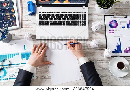Top View Modern Office Workspace With Businessman Hands And Blank White Paper. Flat Lay White Wooden