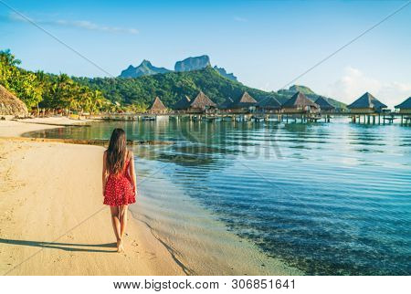 Beach vacation woman walking on Bora Bora island in Tahiti, French Polynesia at sunset with Mount Otemanu and overwater bungalows luxury hotel in the background.