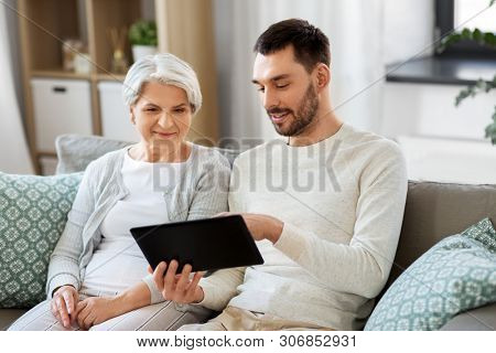 family, technology and people concept - adult son teaching his senior mother how to use tablet computer at home