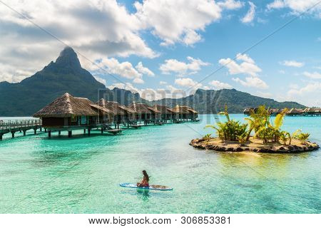 Tahiti luxury resort hotel in Bora Bora ,French Polynesia. Paddleboard leisure activity SUP paddle woman on active vacation in Tahiti, French Polynesia. Mount Otemanu summer holiday.